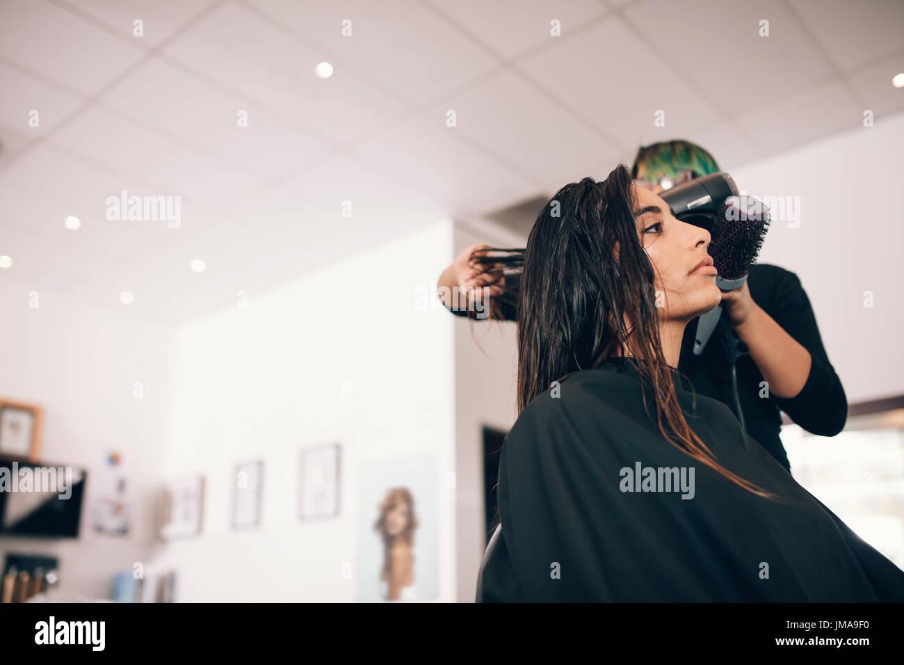 Estilista de cabello femenino utilizando el ventilador y cepillo para el pelo seco. Mujer en un sofisticado salón Foto de stock