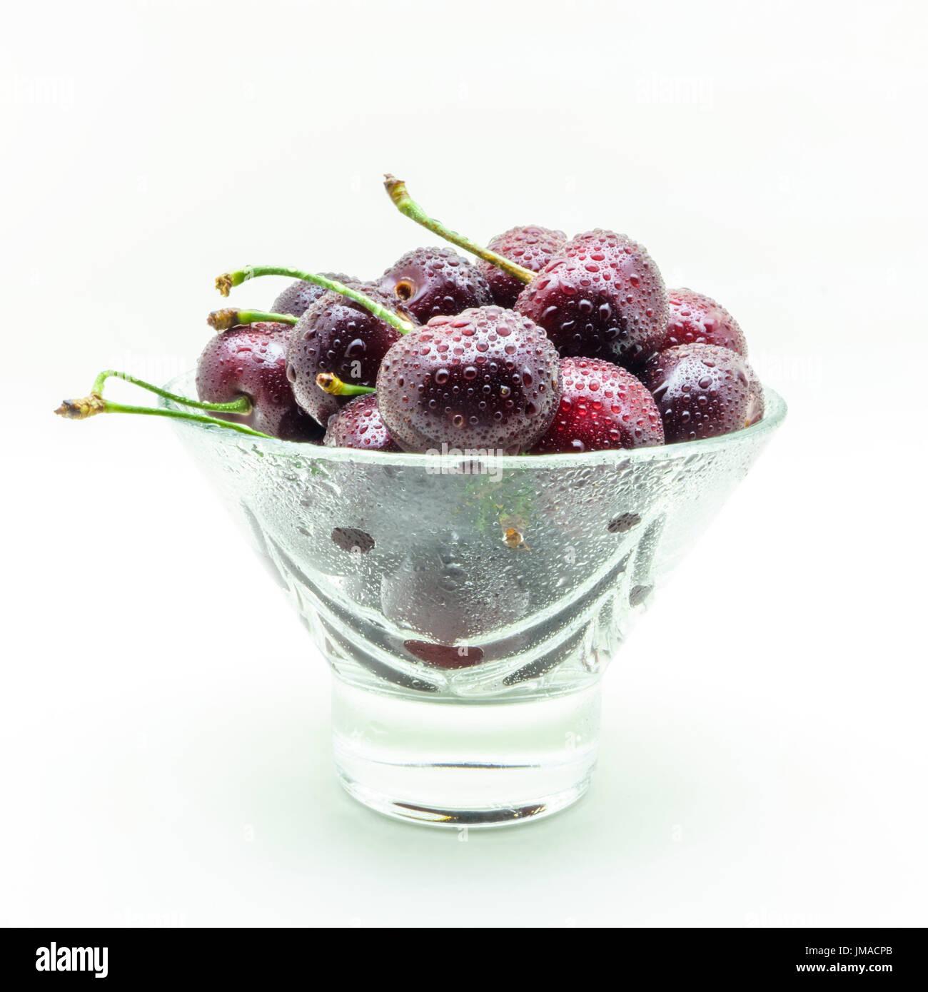 Jarrón de cristal con cerezas húmedo fresco aislado sobre fondo blanco. Foto de stock