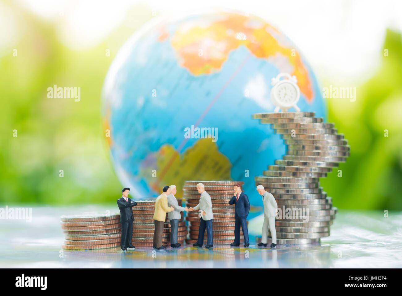 Empresario en miniatura handshaking con Globe y crecientes pilas de monedas fondo usando como el compromiso, el acuerdo, la inversión y la cooperación. Imagen De Stock