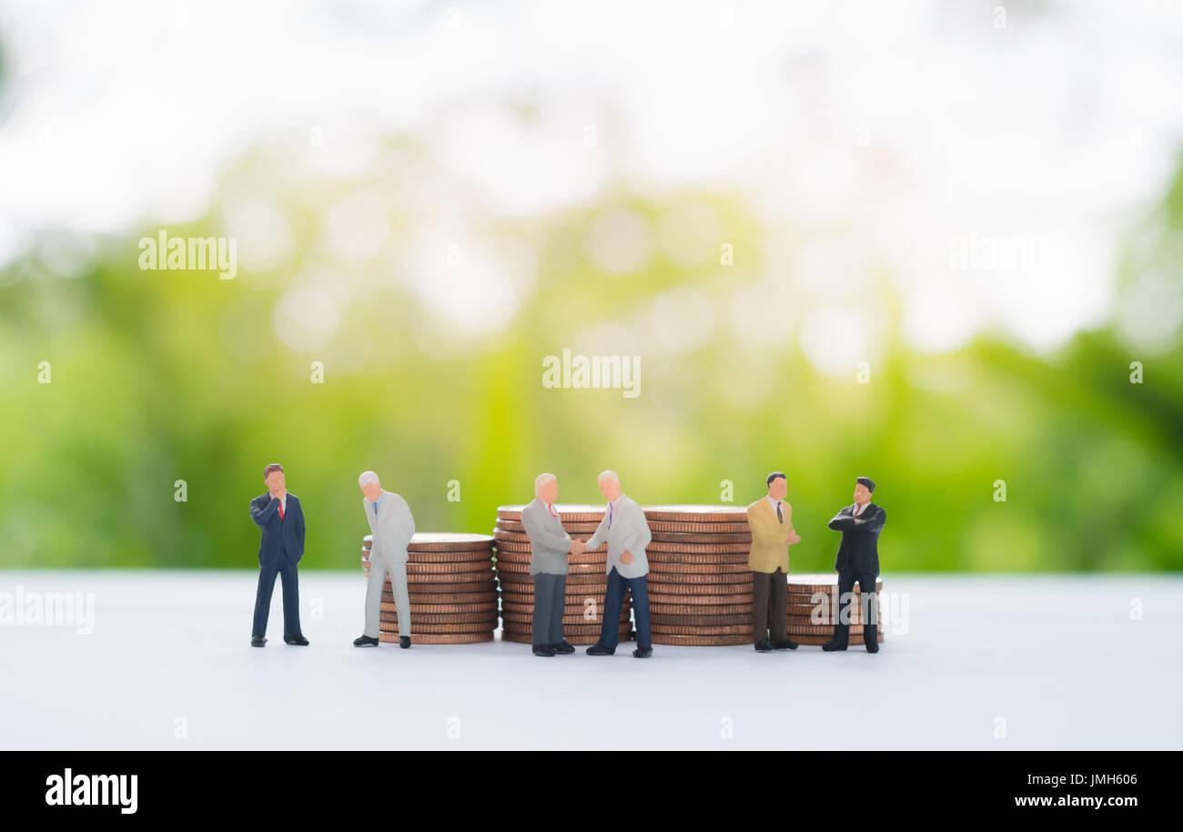 Pila de monedas detrás del empresario en miniatura handshaking, el debate, la negociación utilizando como fondo, el acuerdo, el compromiso de inversión y colaboración Imagen De Stock