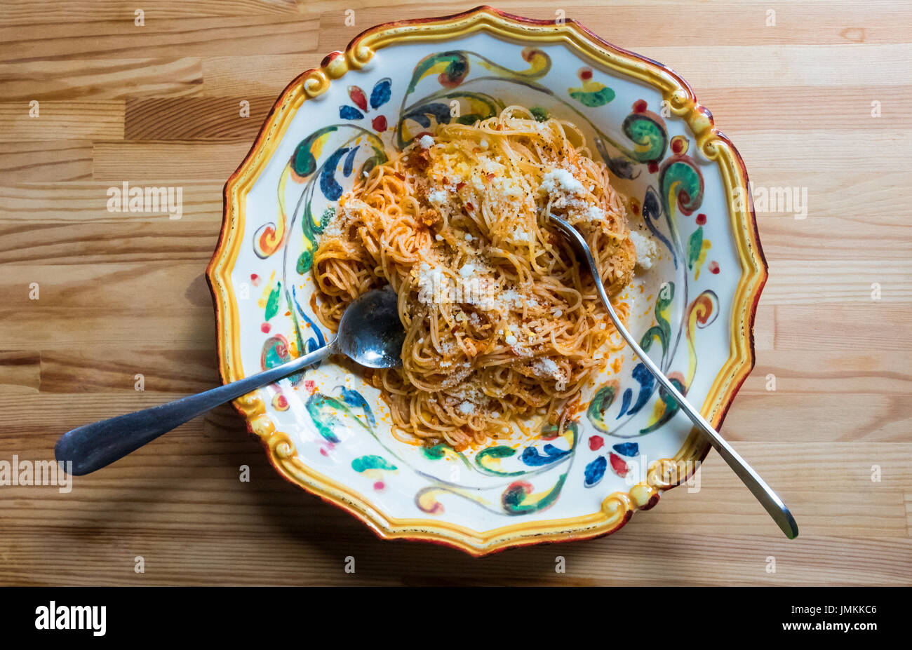 Spaghettini, o pasta fina, con tomate, cebolla, mantequilla y parmigiano reggiano (parmesano) de queso. Imagen De Stock