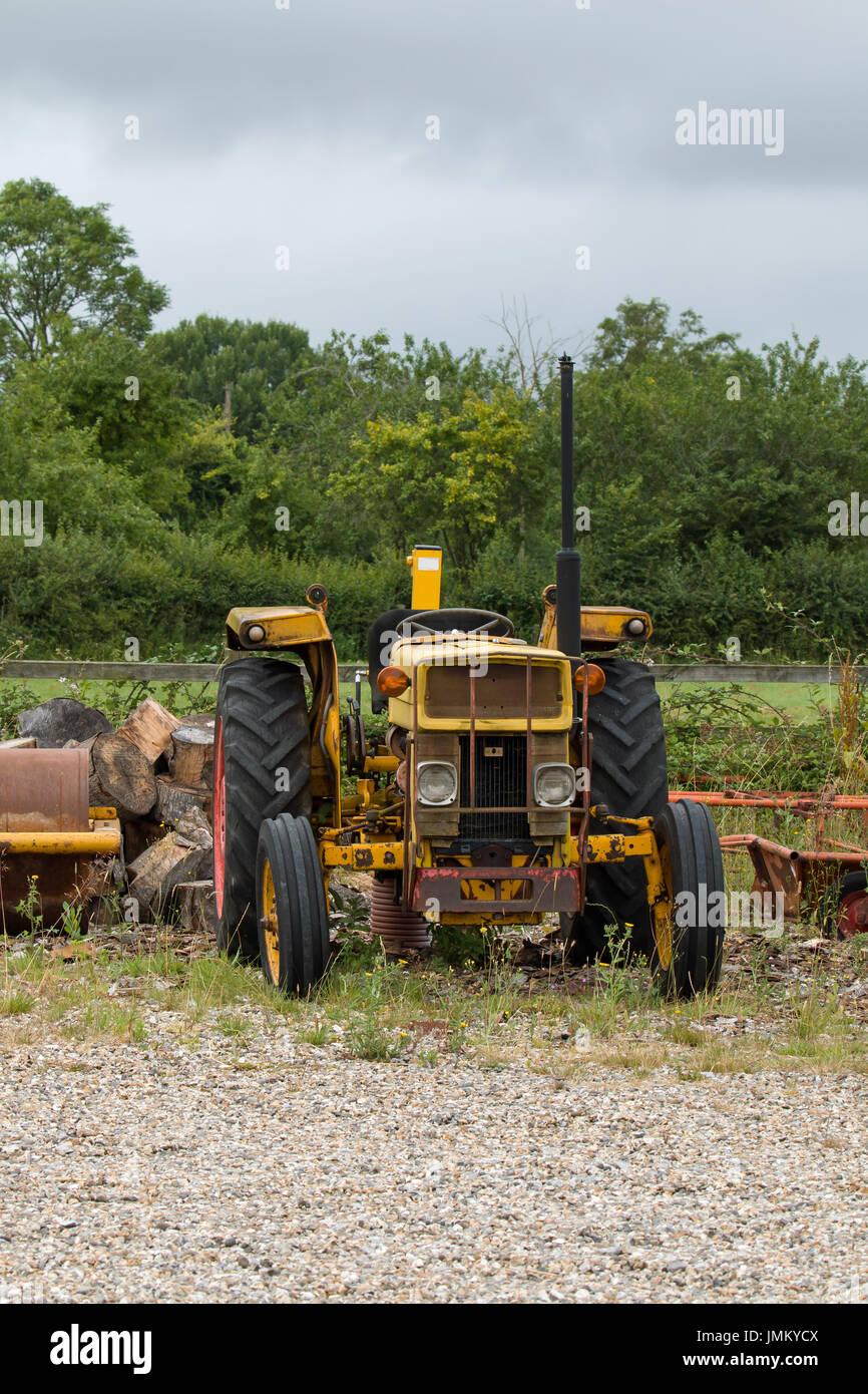 Viejo tractor amarillo sobre residuos de tierra. Foto de stock