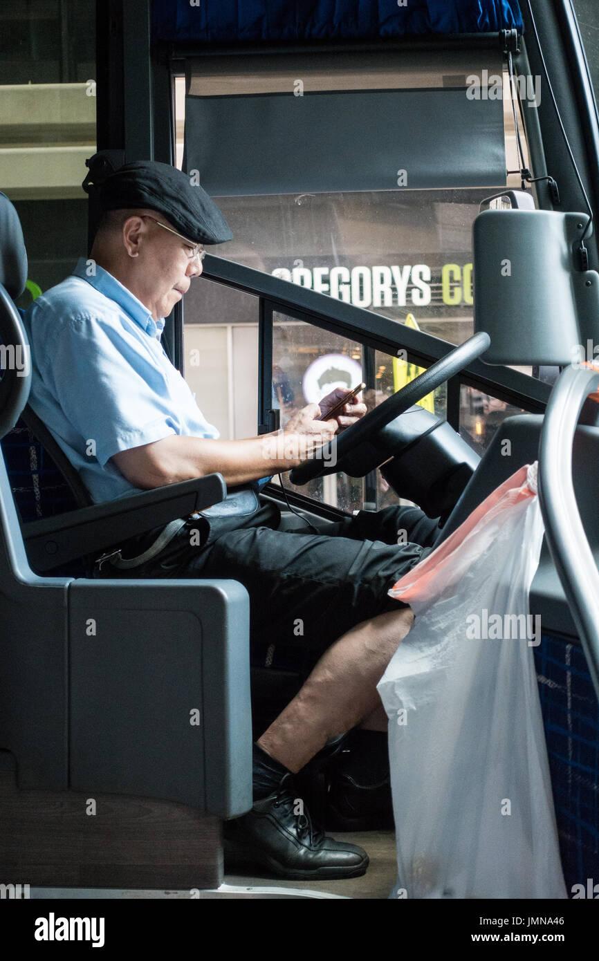 Edad del conductor de autobús asiático mirando su teléfono mientras está tomando un descanso en la calle de la ciudad Foto de stock