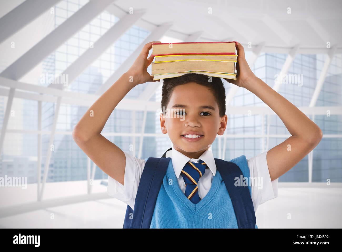 Sonriendo colegial llevar libros en la cabeza sobre fondo blanco contra la moderna habitación con vistas a la ciudad Foto de stock