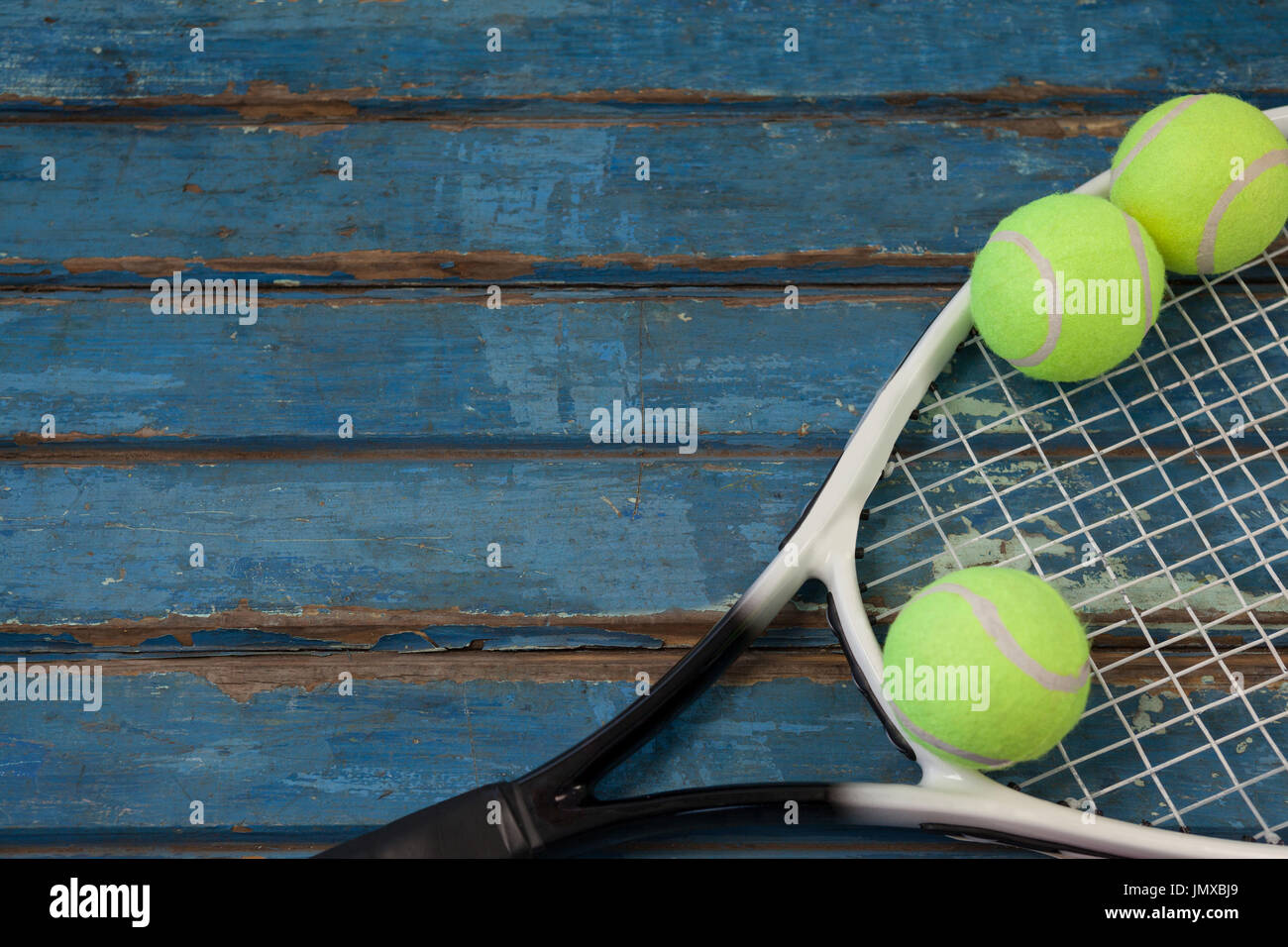 9e6a3097df Un alto ángulo de visualización de raqueta de tenis y las bolas sobre la  mesa de madera