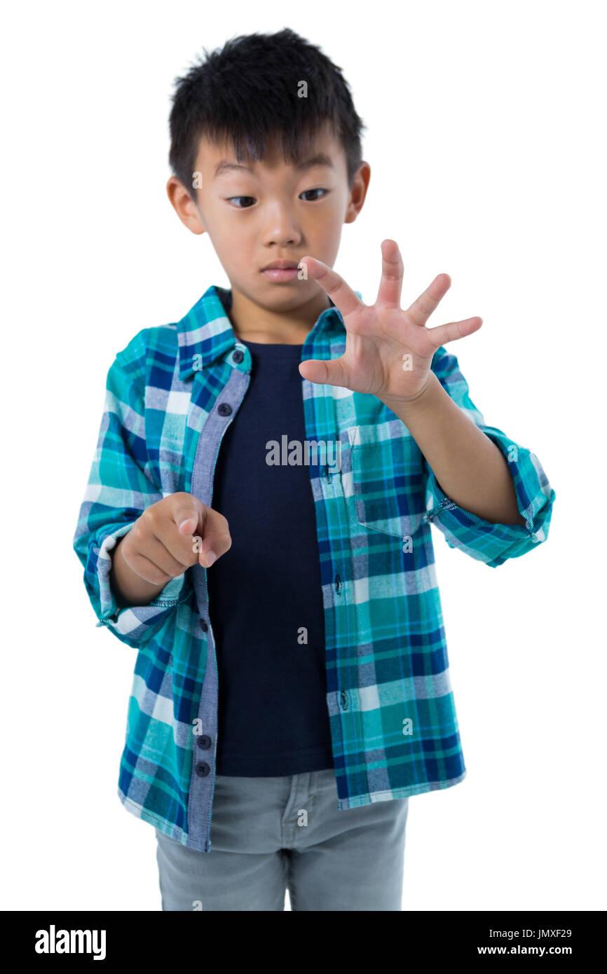 Chico simulando tocar una pantalla invisible contra el fondo blanco. Imagen De Stock
