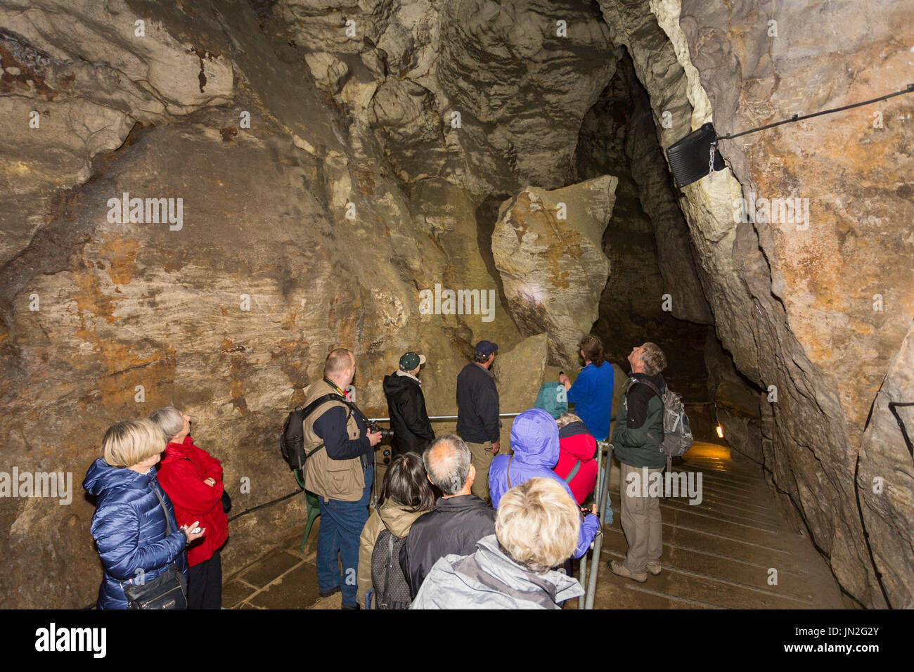 Un grupo de turistas se muestran las 20 toneladas de piedra de equilibrio en el sistema Blue John caverna, nr Castleton, Peak District, Derbyshire, Inglaterra, Reino Unido. Foto de stock