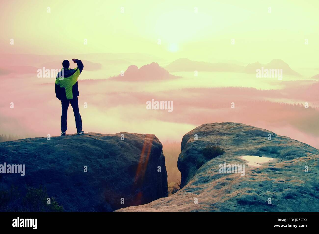 Momento de soledad. Hombre sobre la roca imperios y vigilar el brumoso o nublado mañana valle. Imagen De Stock