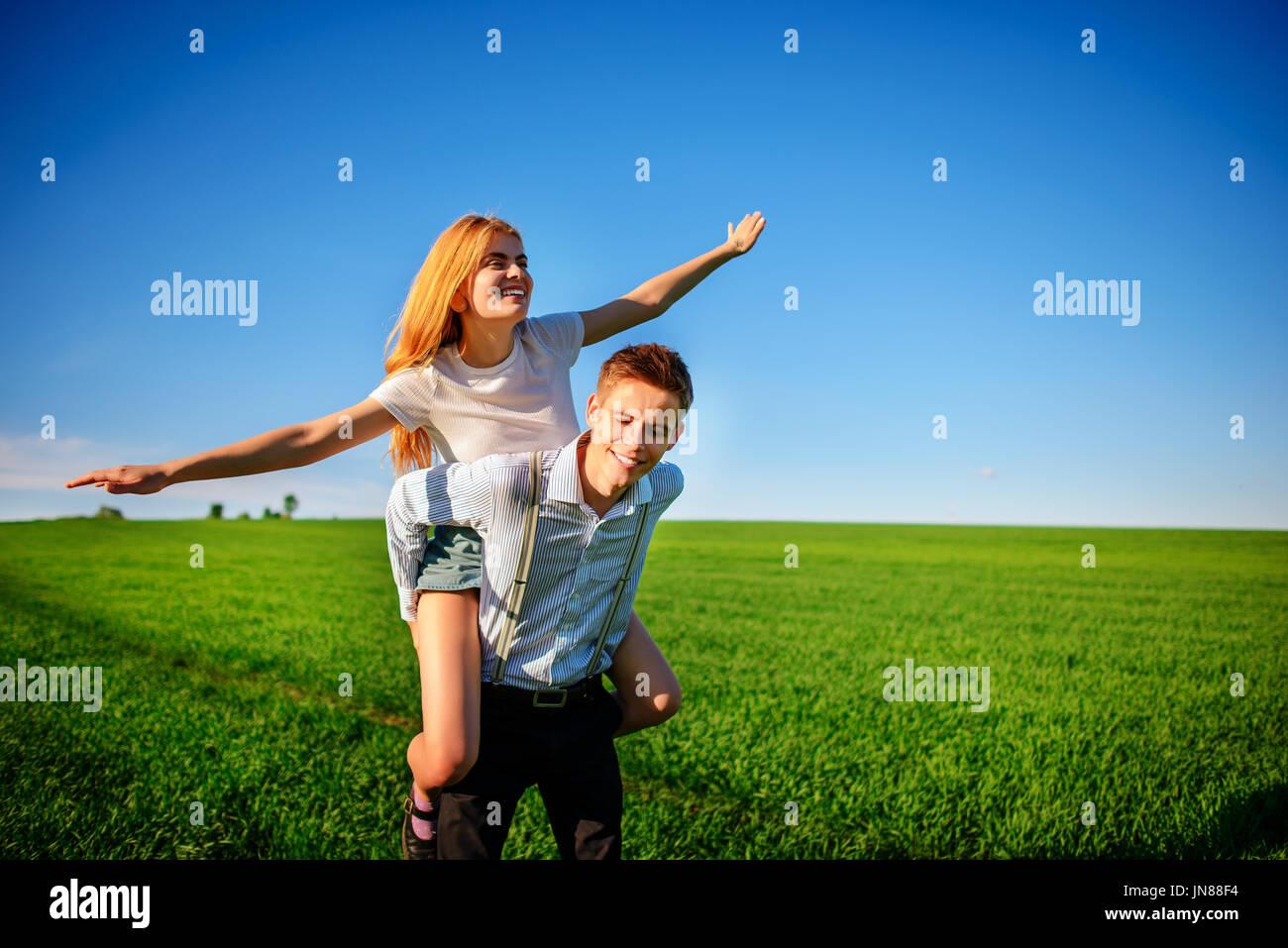 Hombre sonriente sosteniendo en su espalda feliz mujer, que saca sus brazos y simula un vuelo contra el fondo del cielo azul y el verde de la FIE Imagen De Stock
