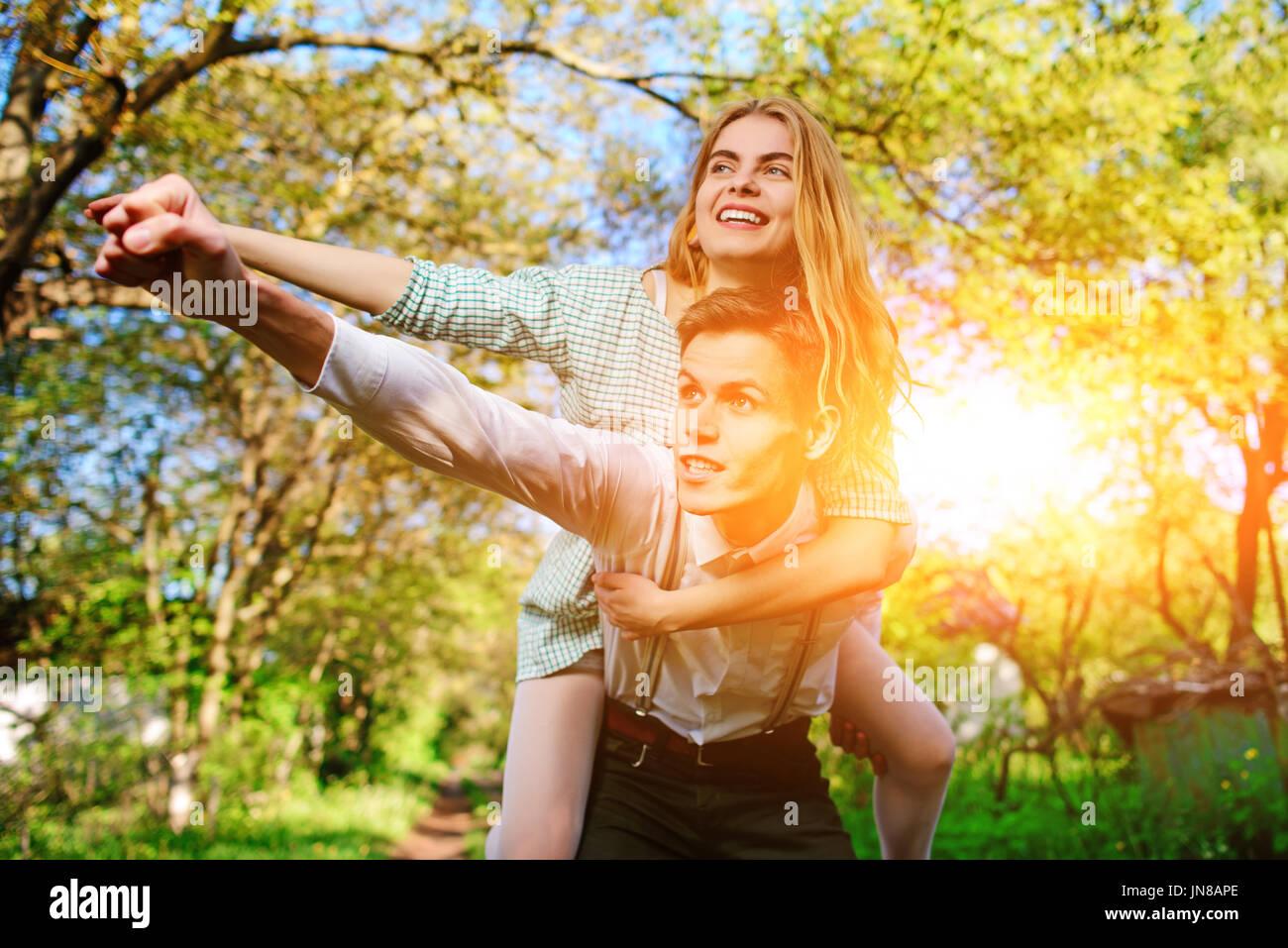 Retrato de pareja feliz levantando sus manos al aire libre. Imagen De Stock