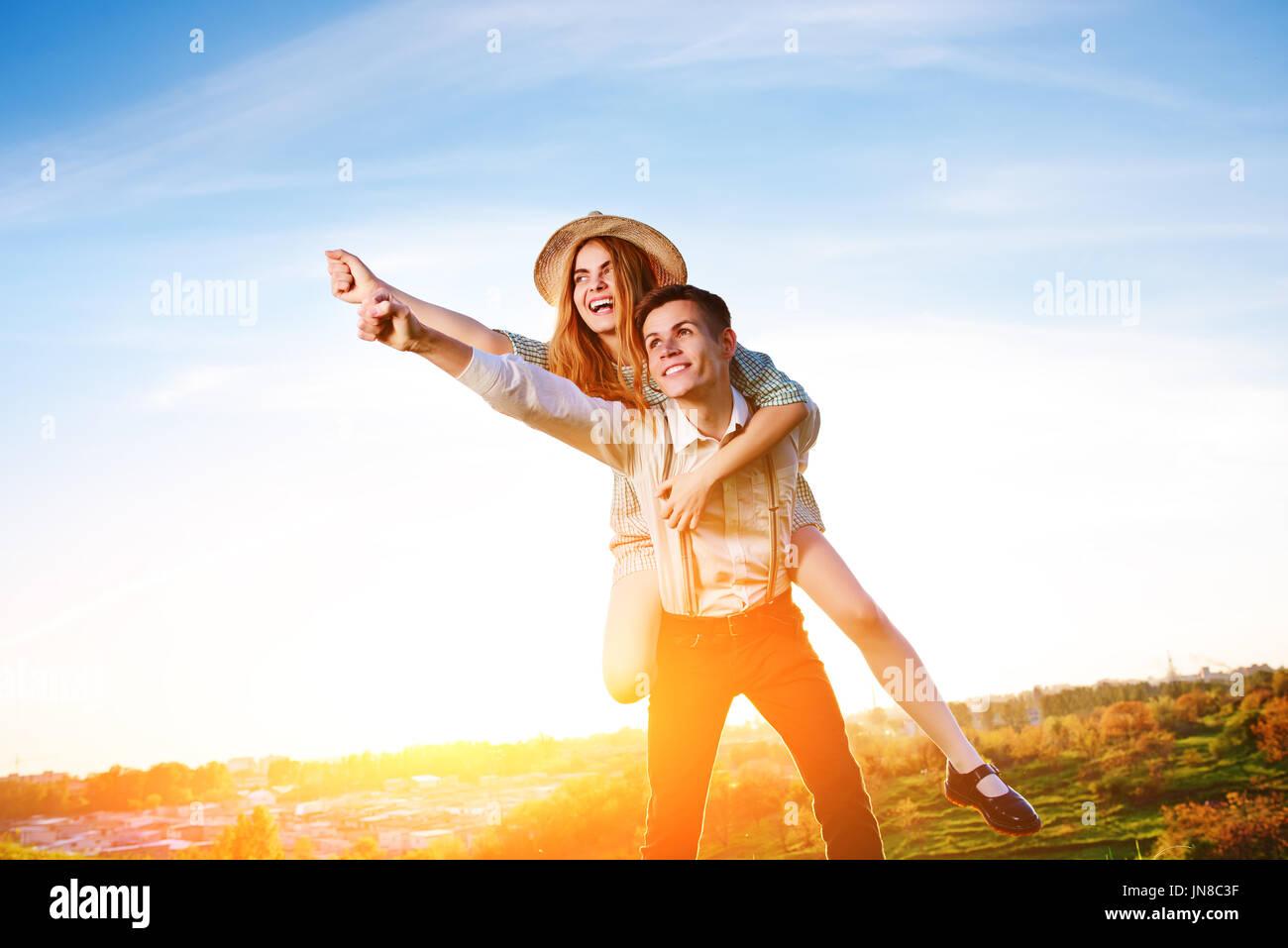Joven aprovechar su novia feliz con la mano levantada. Los amantes de la alegre soñando. Imagen De Stock