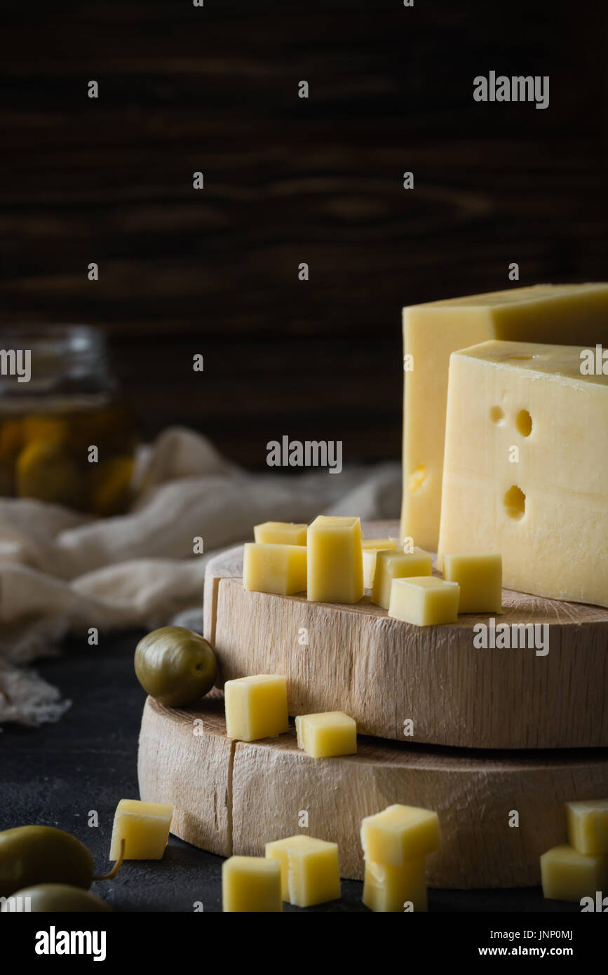 Queso amarillo duro sueco con agujeros picados en rodajas de madera con aceitunas verdes sobre fondo rústico oscuro Imagen De Stock