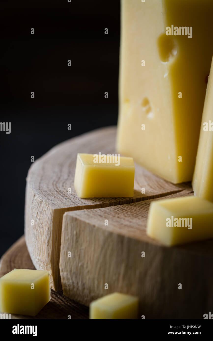 Cerca de queso amarillo duro sueco con agujeros picados en rodajas de madera oscura sobre fondo rústico Imagen De Stock