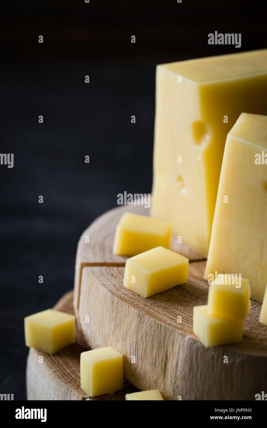 Acercamiento de queso amarillo duro sueco con agujeros picados en rodajas de madera oscura sobre fondo rústico Imagen De Stock