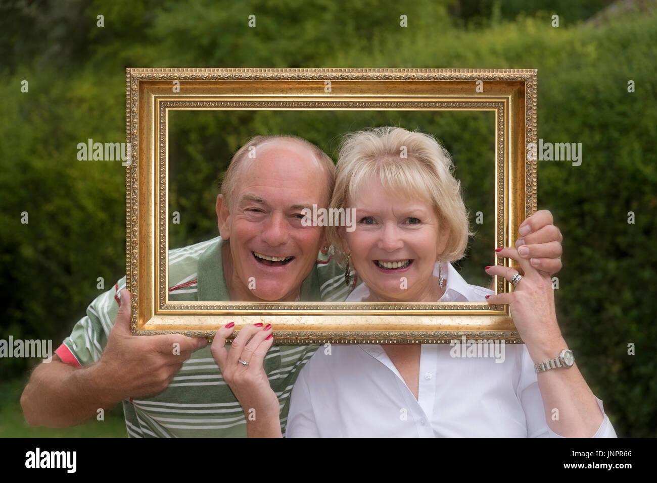 Retrato de una pareja de ancianos jugando con un marco de imagen en ...