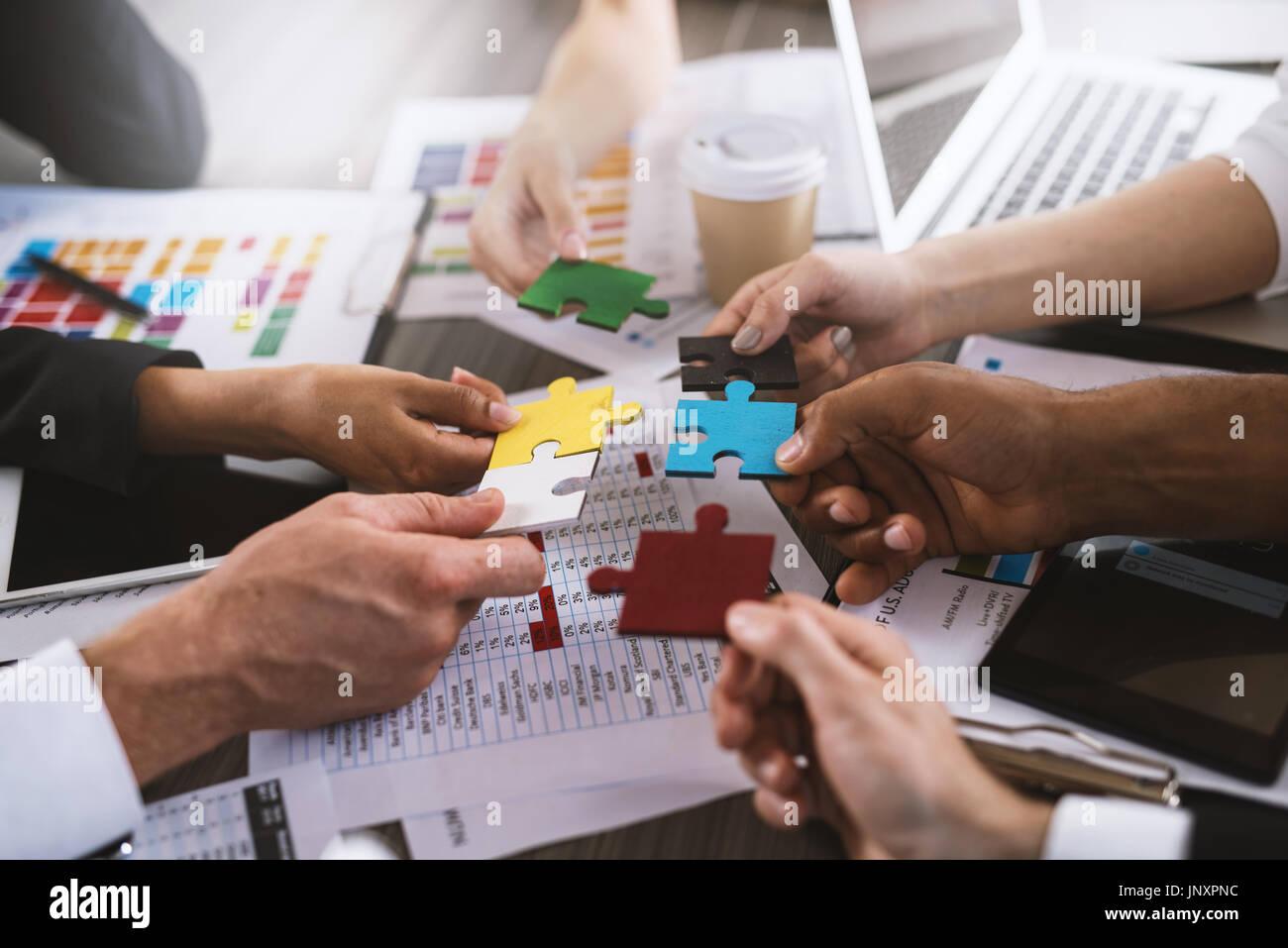 Trabajo en equipo de colaboradores. Concepto de integración y arranque con piezas de rompecabezas Imagen De Stock