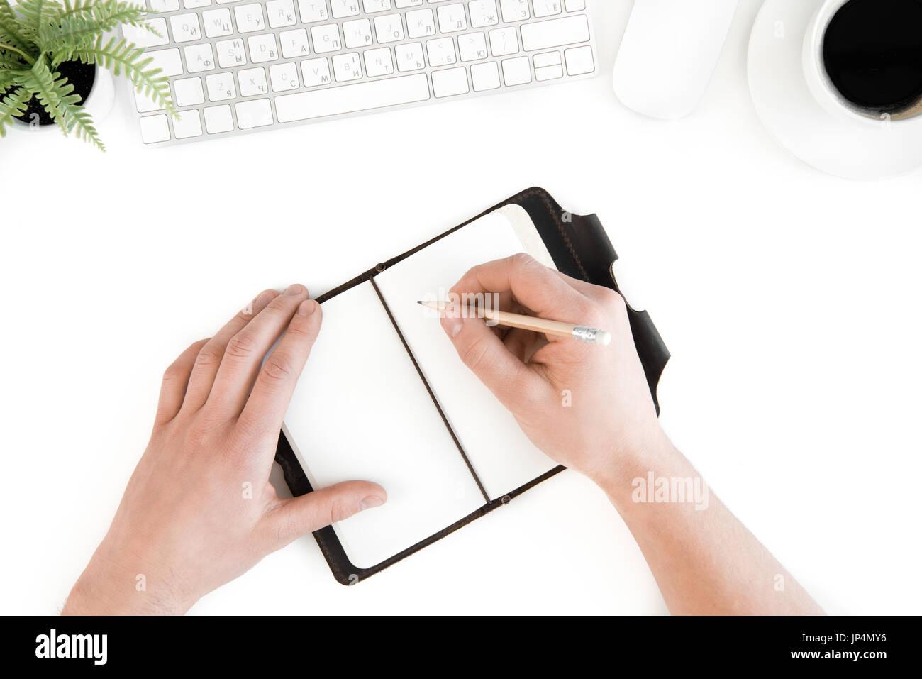 Vista superior de la persona escrito en diario en el lugar de trabajo con el teclado de ordenador, aislado en blanco Imagen De Stock