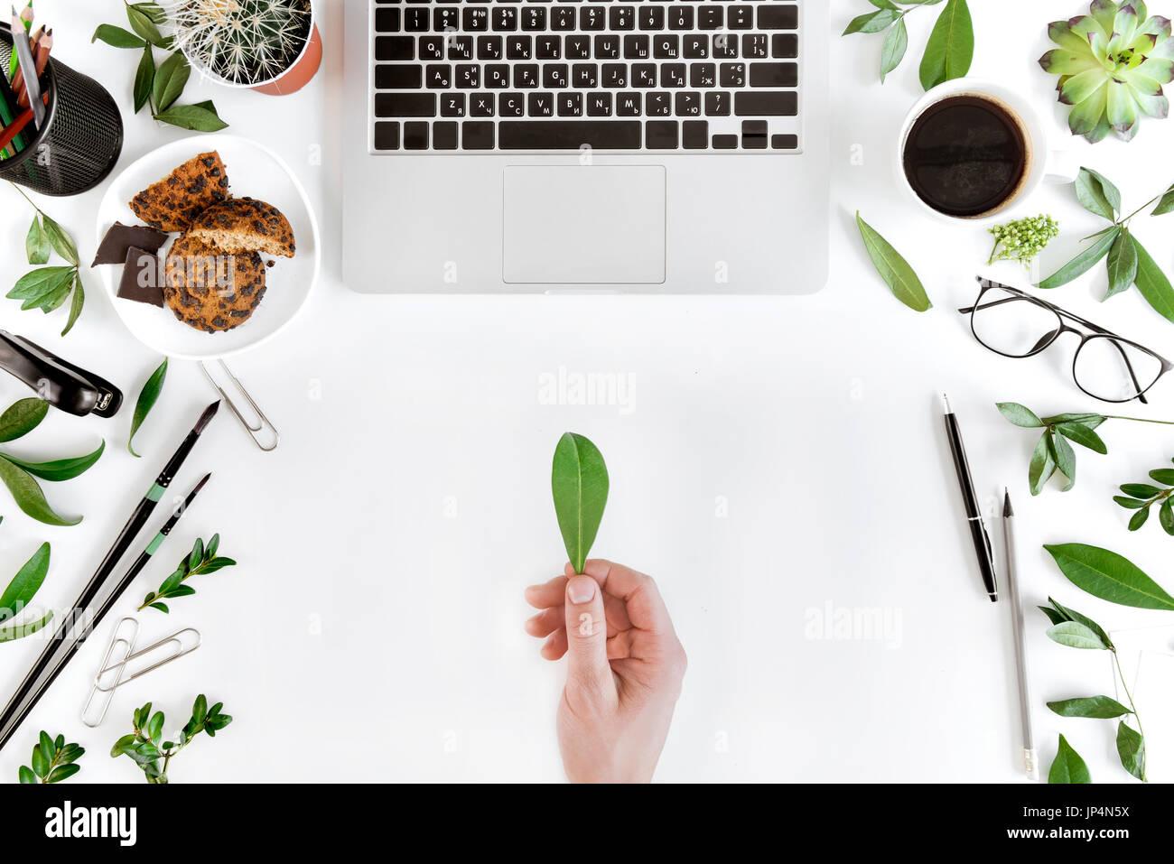 Vista superior parcial de la persona titular de hojas verdes en el lugar de trabajo con un ordenador portátil, la taza de café, de hojas verdes y suministros de oficina, comunicación inalámbrica concepto Imagen De Stock