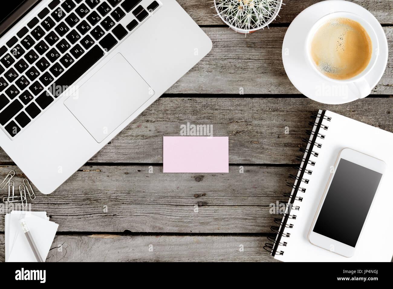 Vista superior de dispositivos digitales inalámbricos y tarjeta en blanco en el lugar de trabajo Foto de stock