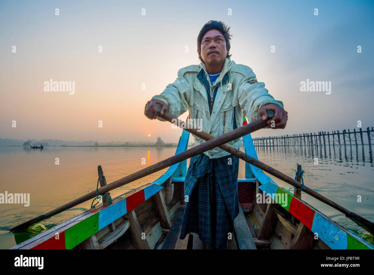 Amarapura, región de Mandalay, Myanmar. Hombre remo en su colorido barco sobre el lago Taungthaman al amanecer, con el Puente U Bein en el fondo. Imagen De Stock