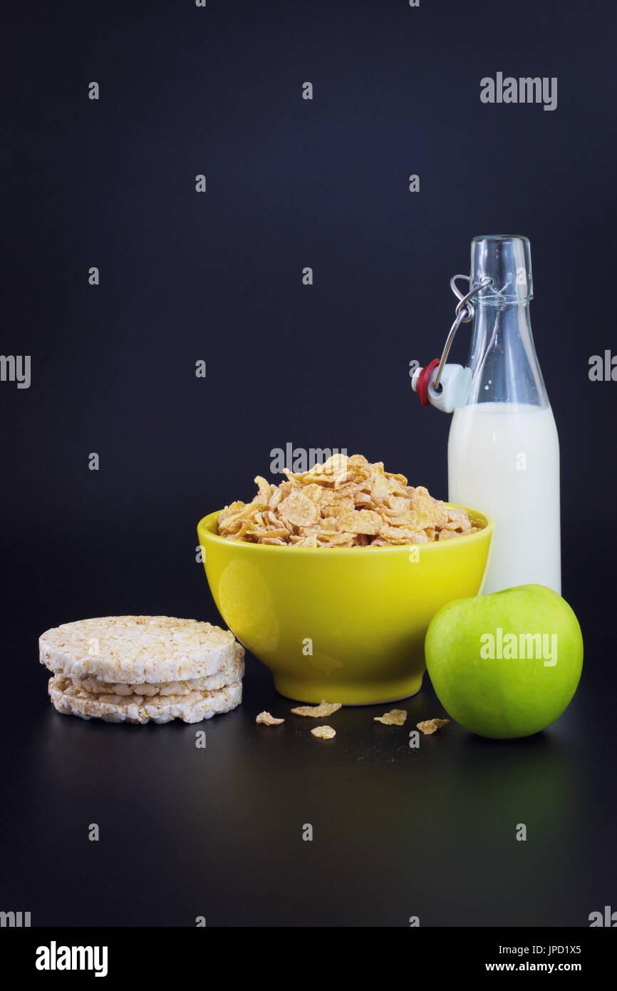 Desayuno energético para la dieta copos de cereales de leche de maíz y manzana verde sobre fondo negro con espacio de copia Imagen De Stock