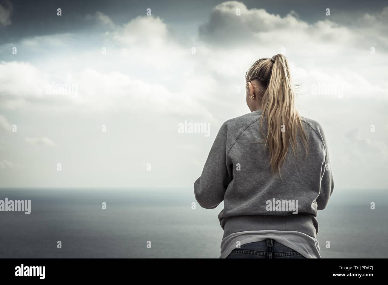 Mujer sonriente joven rubia retrato con paisaje de las montañas borrosa sobre fondo en días nublados Imagen De Stock