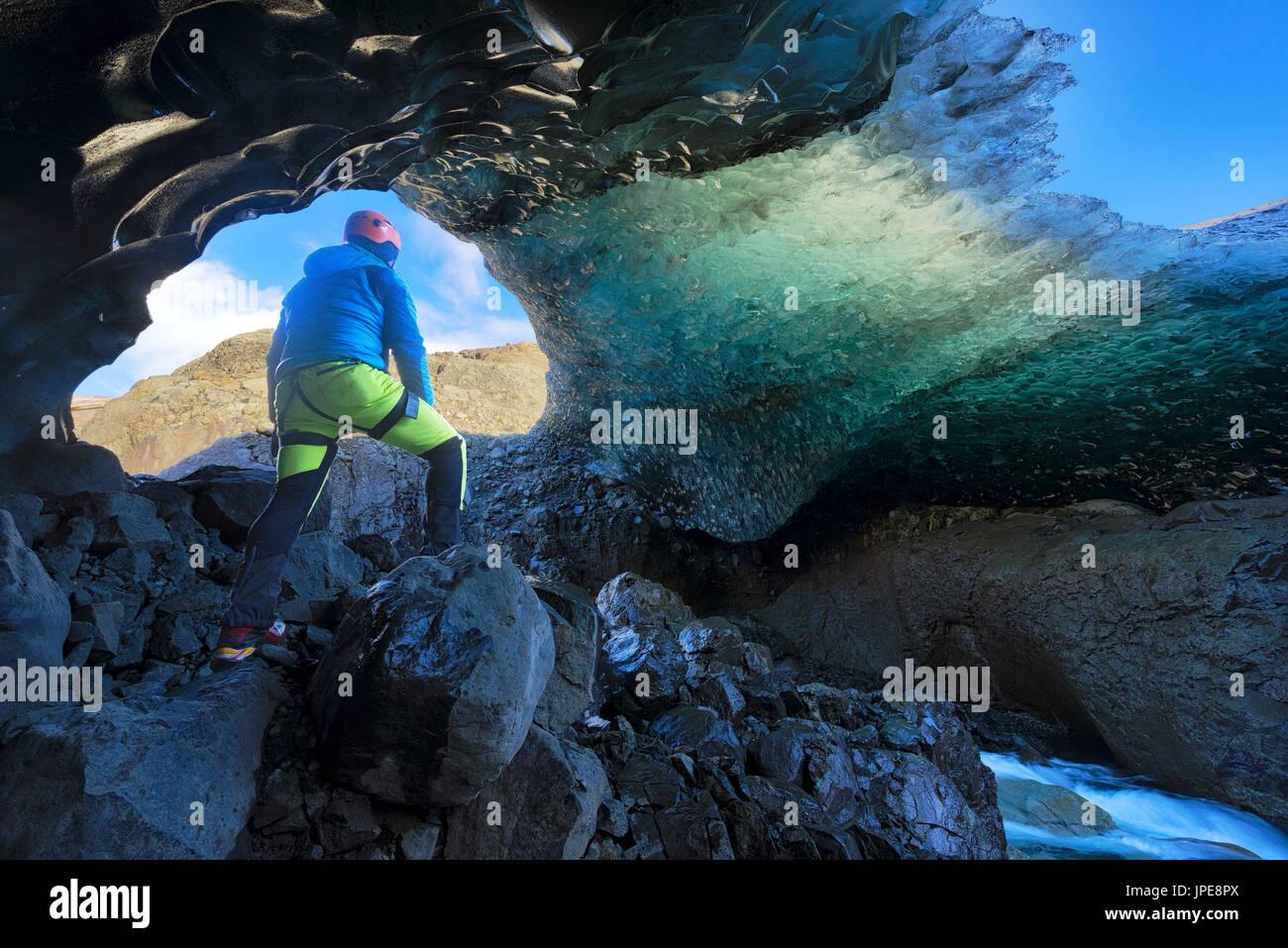 Parque Nacional Skaftafell, Islandia, Europa. Hombre admirar la cueva de hielo cristal azul bajo el glaciar Vatnajokull en invierno. Imagen De Stock