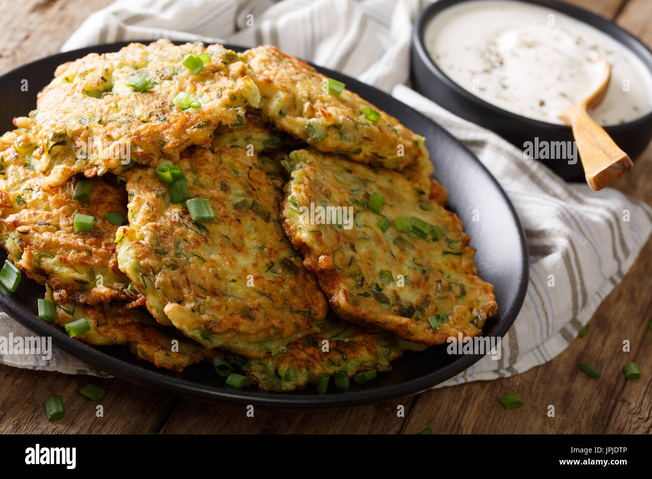 Tortitas de calabacín recién cocinados con crema agria de cerca en la tabla horizontal. Imagen De Stock