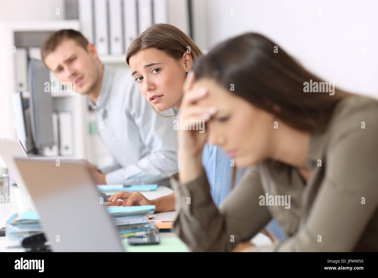 Los trabajadores tristes mirando a un colega que está frustrado leer malas noticias en línea en Office Imagen De Stock