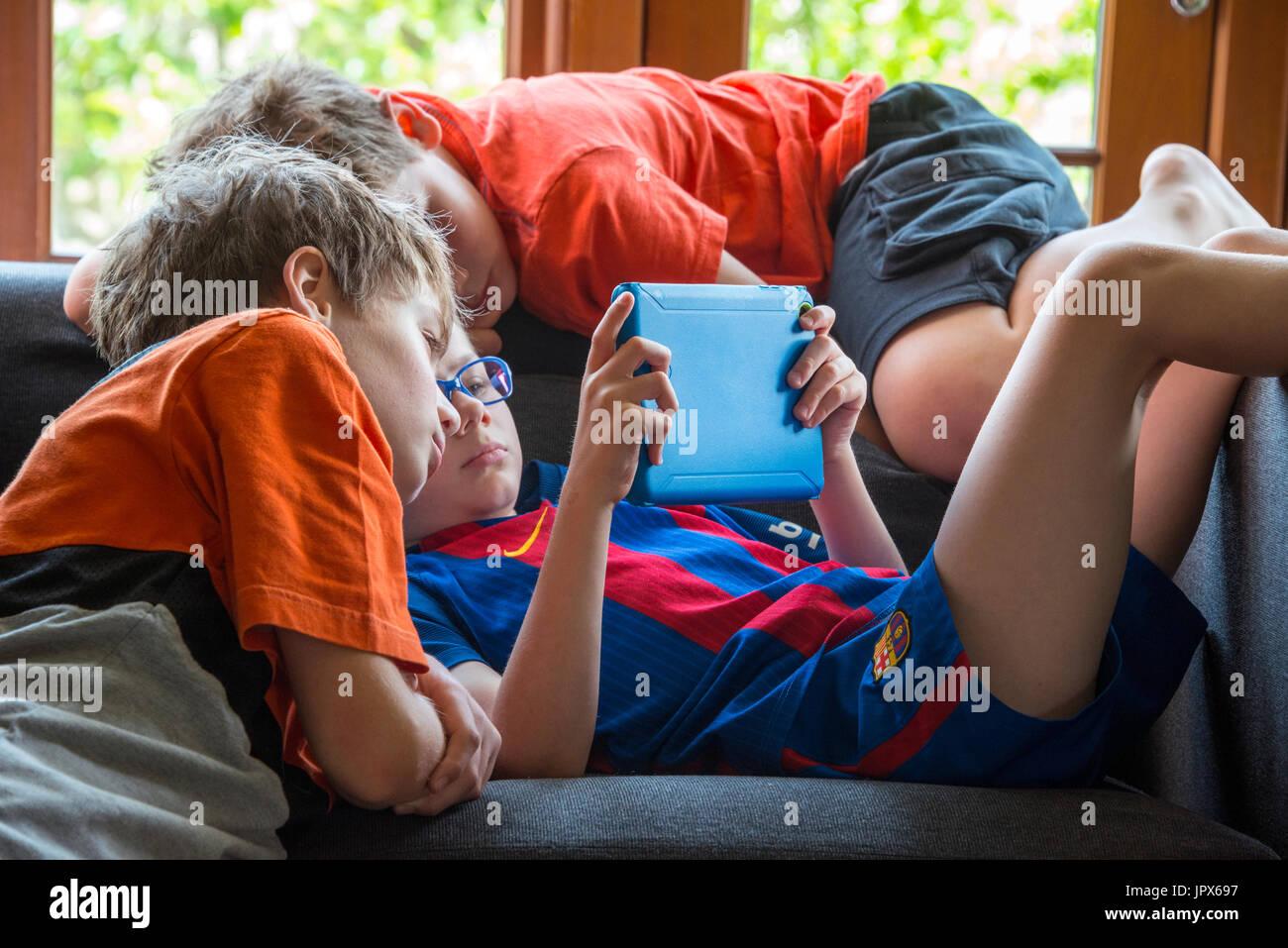 Chico jugar a juegos de ordenador en tablet con otros muchachos, viendo de cerca Foto de stock