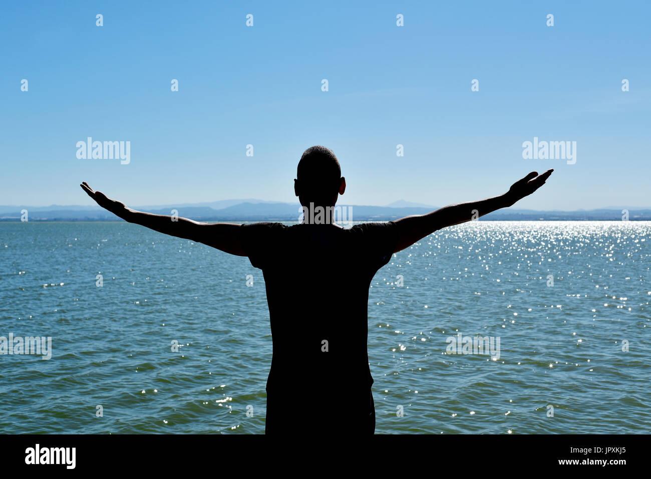 La silueta de un joven hombre caucásico visto desde atrás con sus brazos en el aire delante del océano, sintiéndose libre Imagen De Stock
