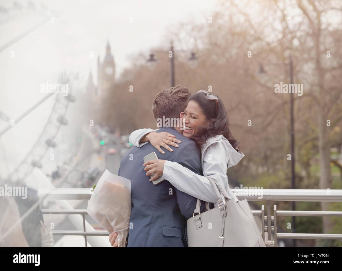 Pareja sonriente abrazando, novio sorprendente novia con flores en puente urbano, Londres, Reino Unido. Imagen De Stock