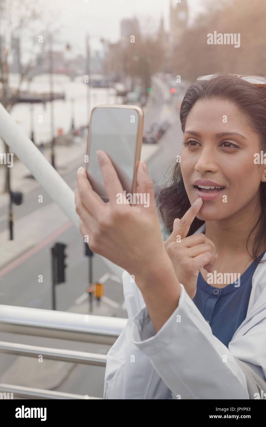 Comprobación de mujer maquillaje con teléfono con cámara en el puente urbano, Londres, Reino Unido. Imagen De Stock