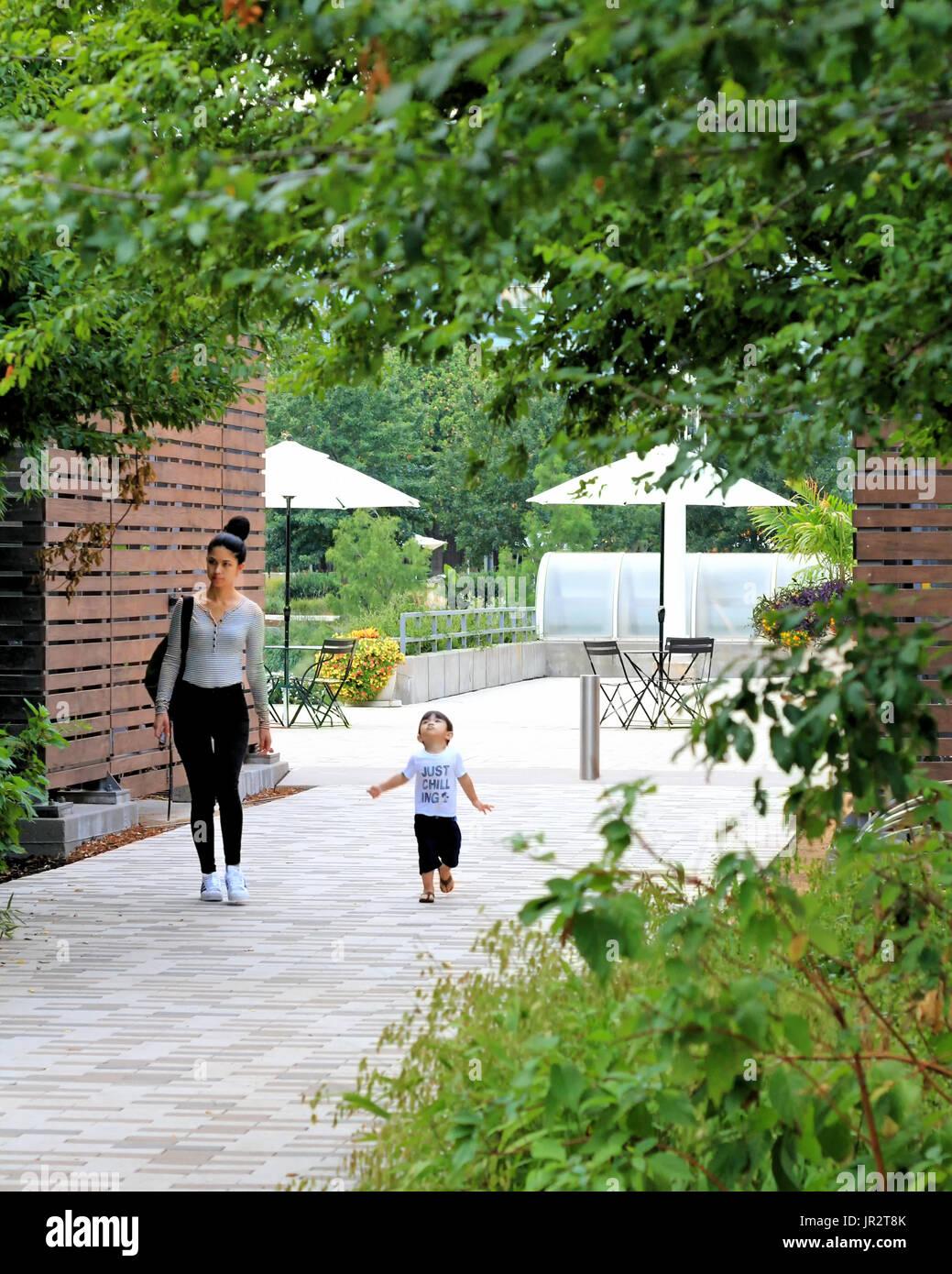 Una mujer joven y un niño chico camina sobre la acera cerca de un café de jardín. Imagen De Stock