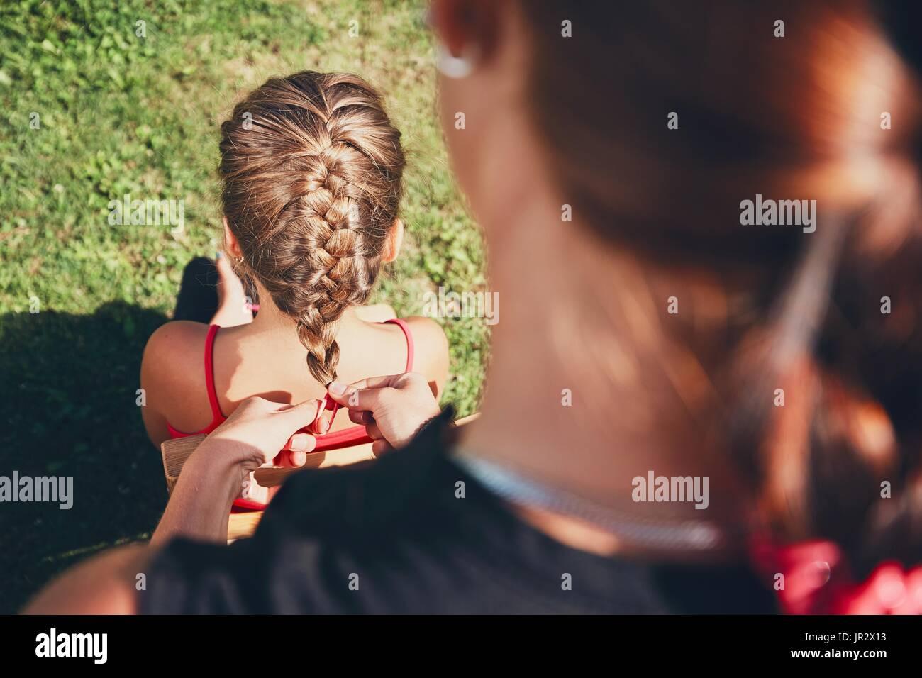 Mujer joven haciendo que el cabello trenzas de la niña en el jardín en el paisaje. Foto de stock
