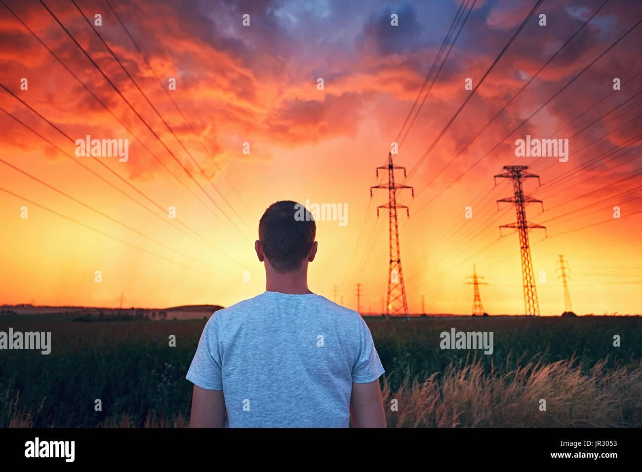 Condiciones meteorológicas peligrosas. Hombre solitario en impresionante tormenta durante la puesta de sol llena de colorido. Imagen De Stock