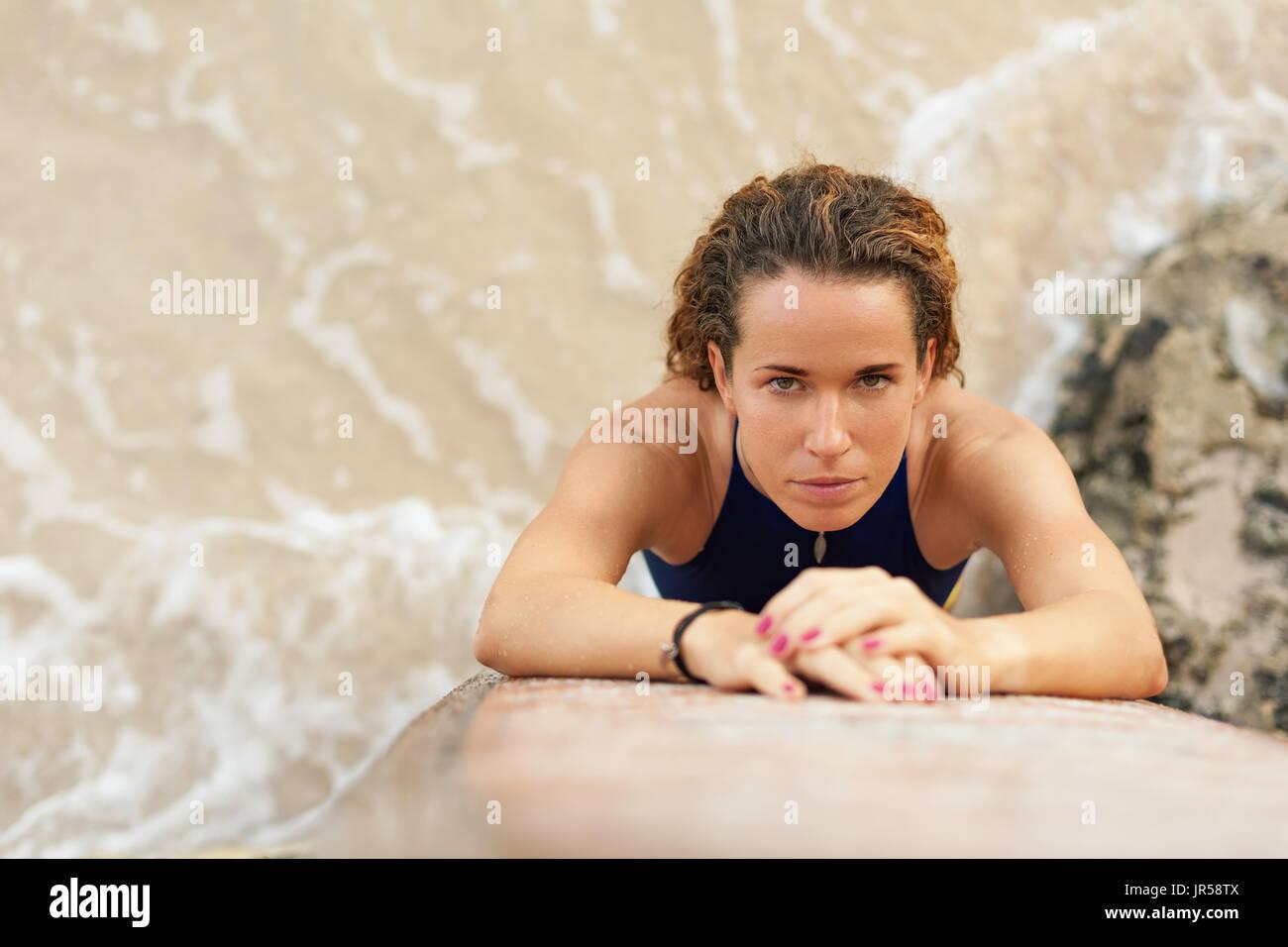 Surfista hermosa chica en bikini celebración surf stand y mirar a la cámara. Vista desde arriba. Las mujeres en el campamento de aventura deportes acuáticos, playa actividades extremas. Imagen De Stock