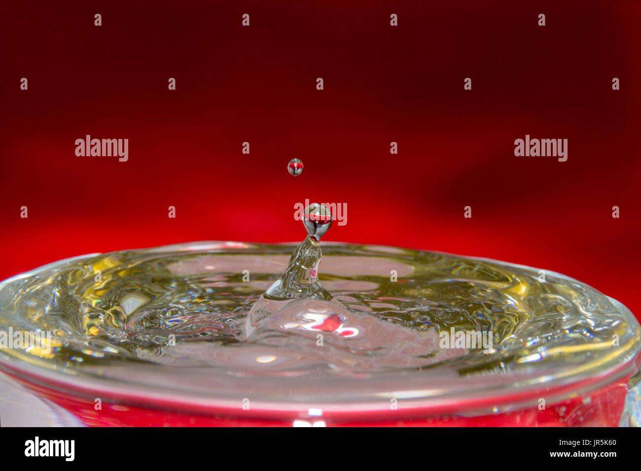 Gota de Agua con fondo rojo y dorado reflejo en el agua, bebidas refrescante y fría con ondas de impacto en el agua, la gota que derrama el vaso con agua Imagen De Stock