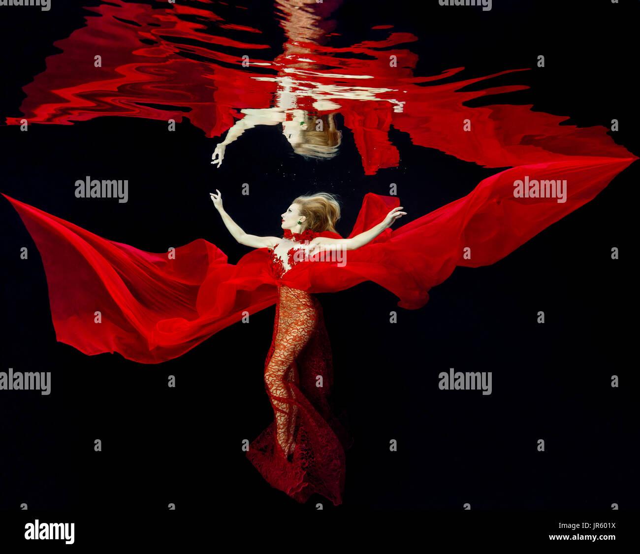 Mujer en un vestido rojo en la piscina Foto de stock