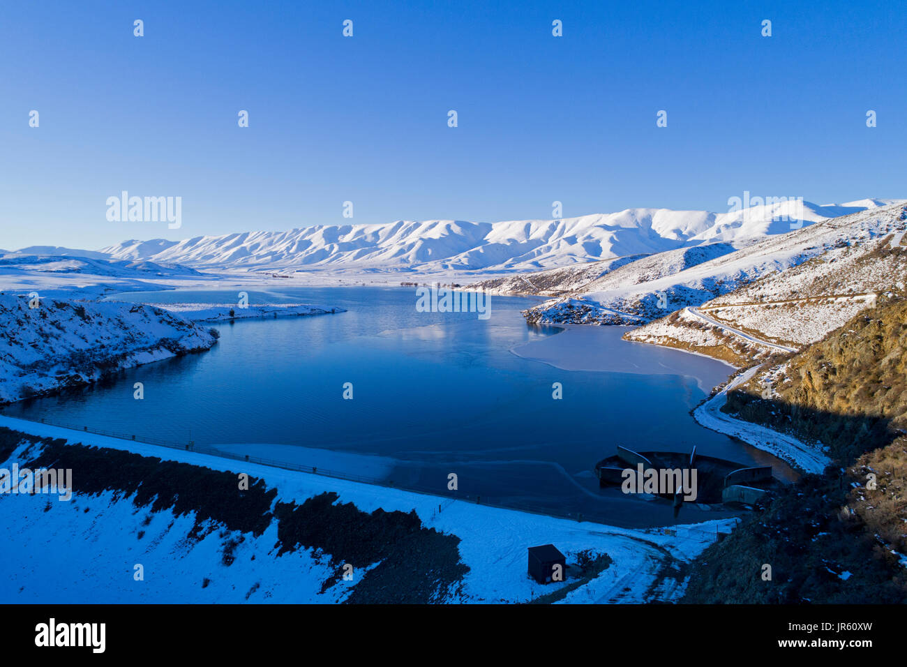 Falls Dam y gama Hawkdun en invierno, Maniototo, Central Otago, Isla del Sur, Nueva Zelanda - antena drone Foto de stock