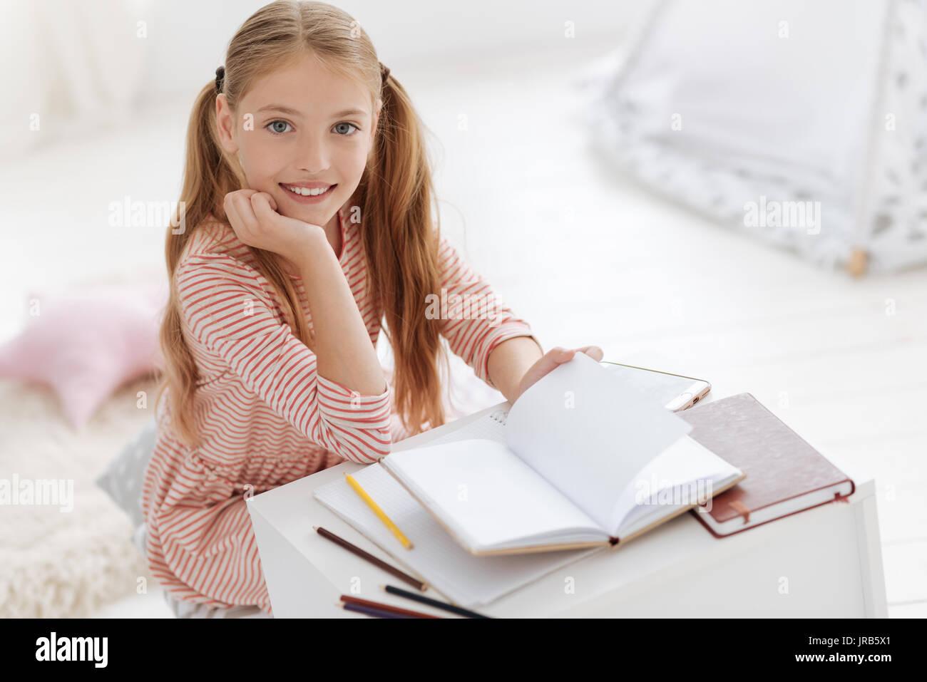 Bonito joven mujer sonriendo a la cámara mientras estudiaba Imagen De Stock