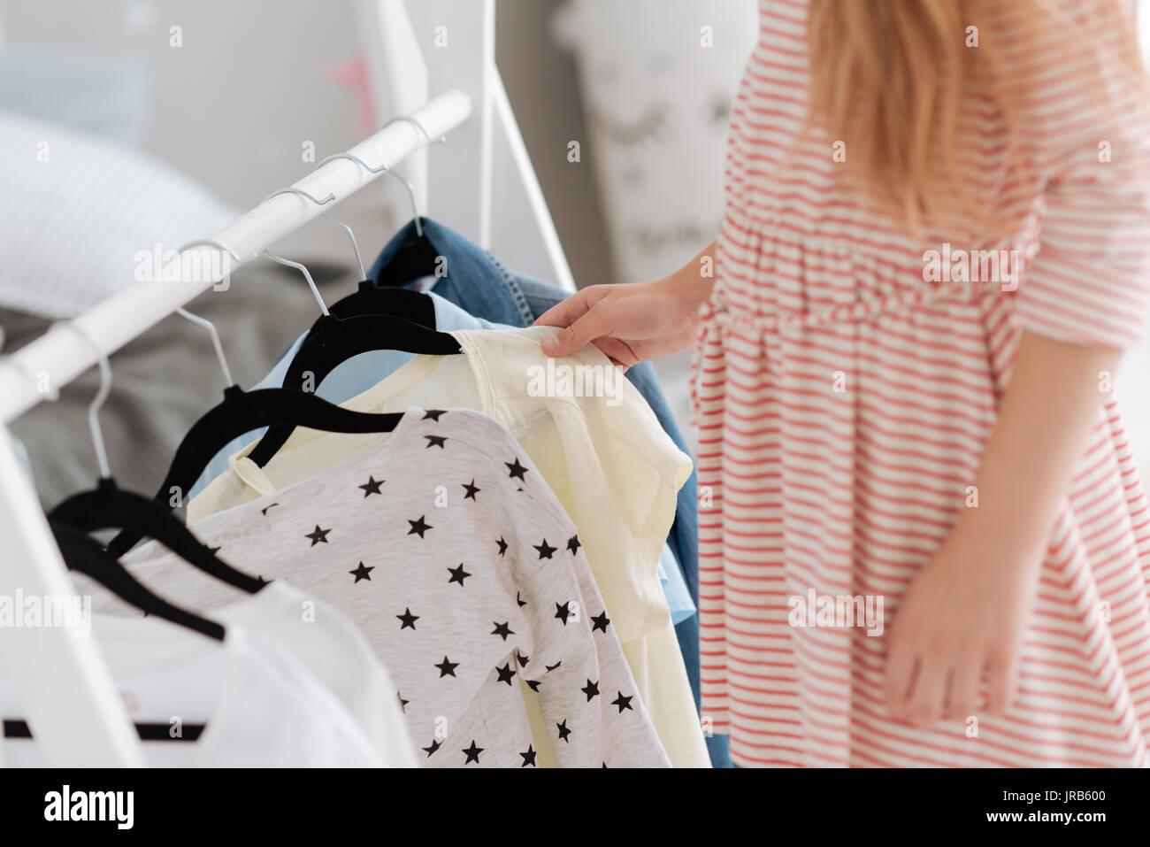Cerca de niña mirando su closet Imagen De Stock