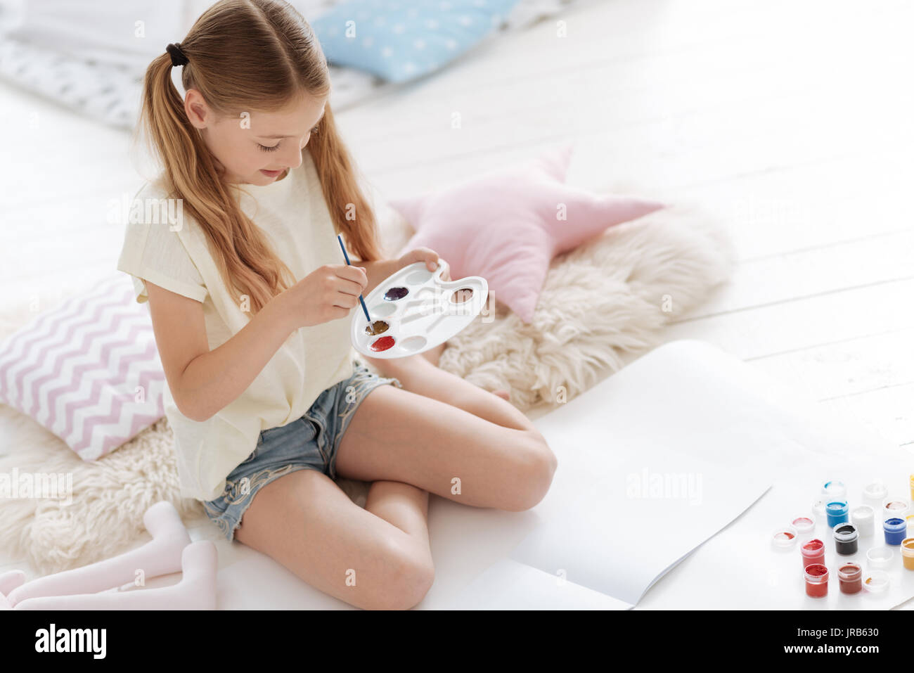 Curioso joven femenina mezclado de pinturas en la paleta Imagen De Stock