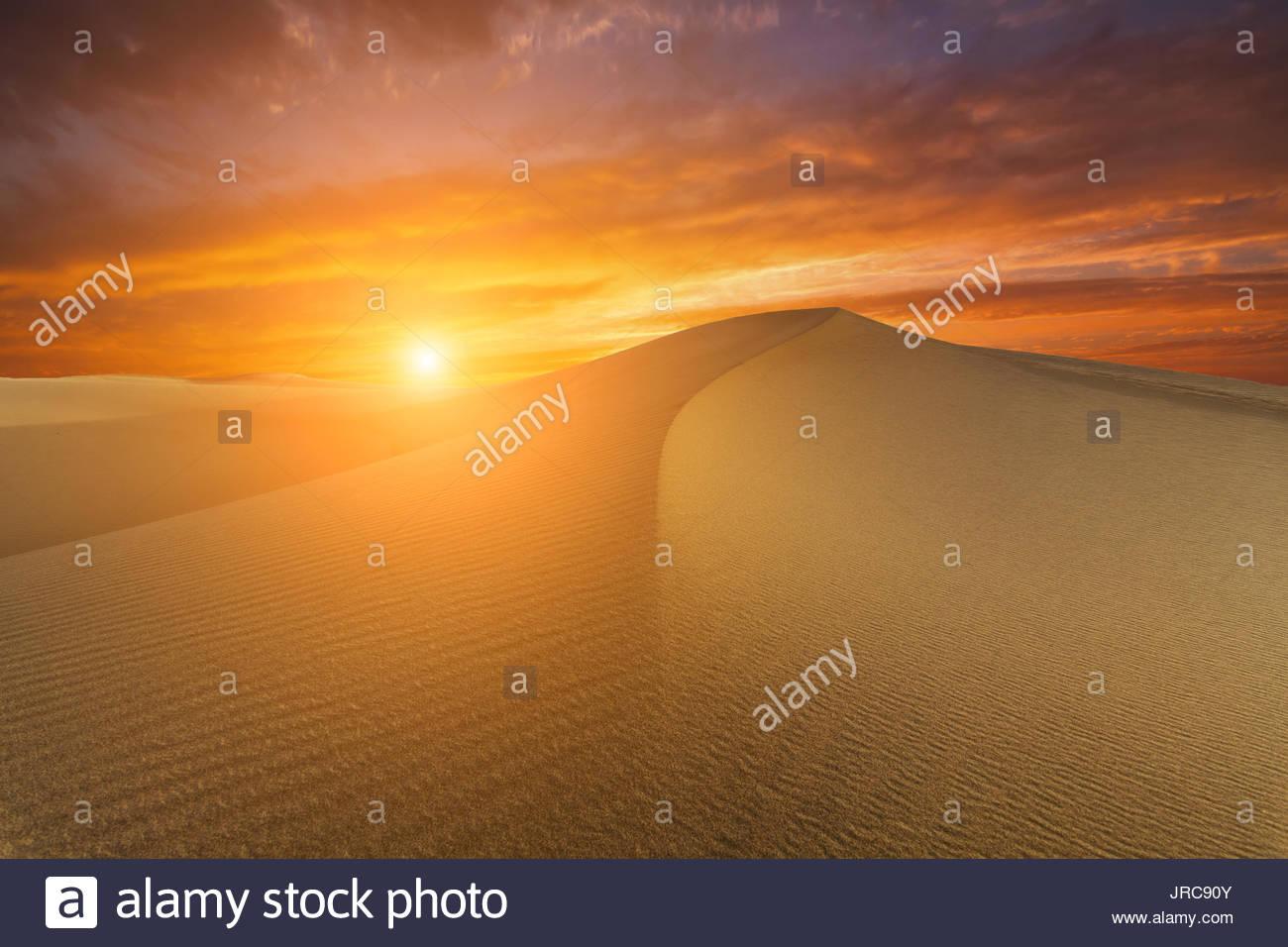 Hermoso paisaje desértico en el fondo de la puesta del sol ardiente. Imagen De Stock
