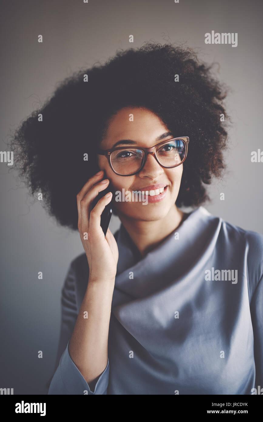Sonriente joven empresaria africana con gafas y aislada en una oficina hablando por un teléfono móvil Foto de stock