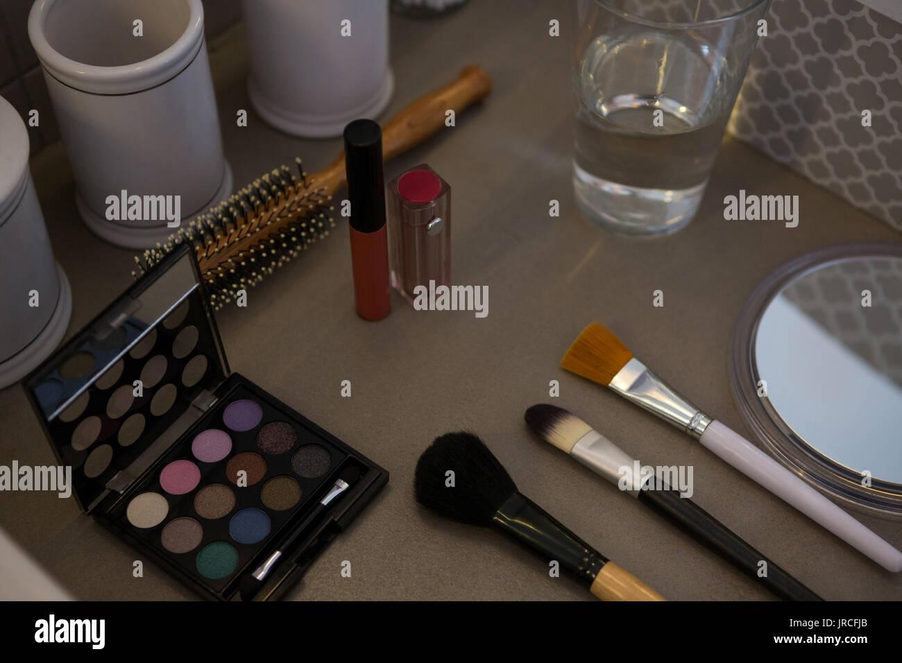 Un alto ángulo de visualización de productos de belleza con vaso para beber en la mesa Foto de stock