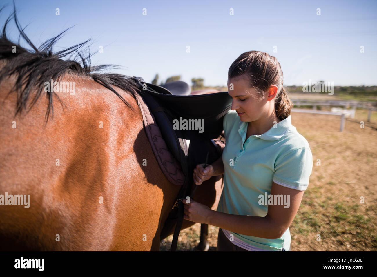 Caballete de sujeción jockey femenino estando de pie en el campo de caballos Foto de stock