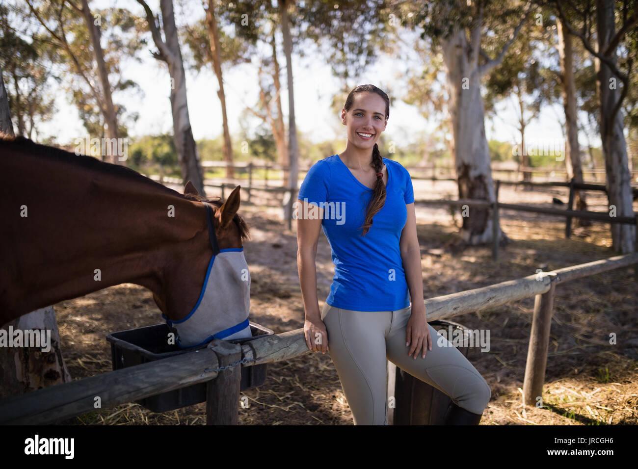 Retrato de mujer de pie a caballo en campo en paddock Foto de stock