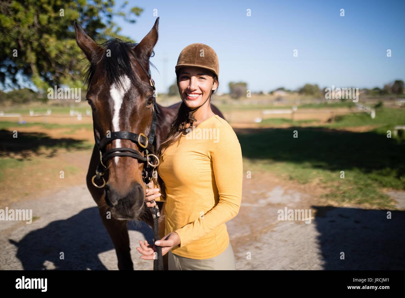 Retrato de mujer confiada jinete con caballo parado en campo Foto de stock