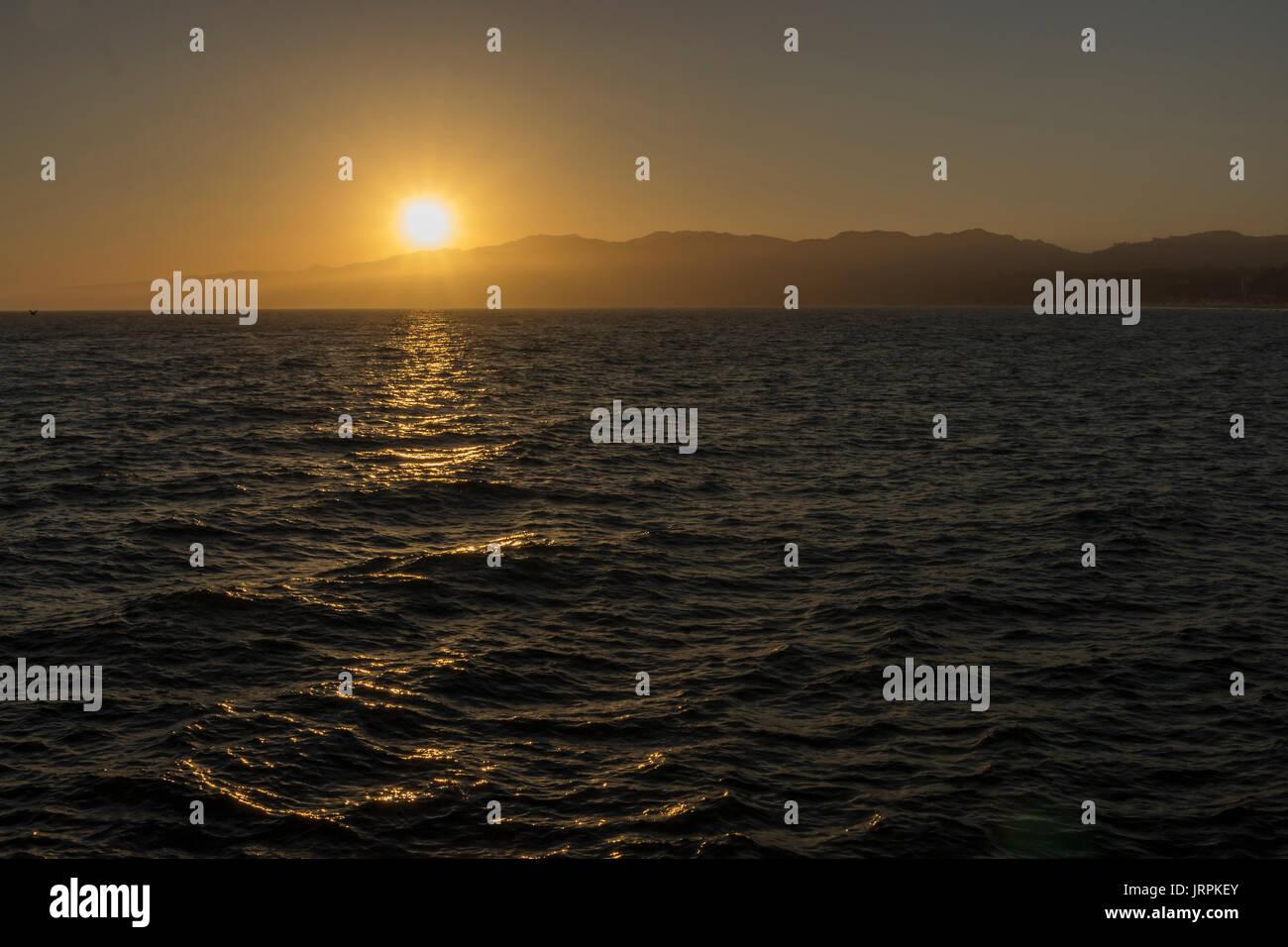 Anochecer en el oceano pacifico, en las pliayas de Santa Mónica, el reflejo del sol en el agua, deja un camino de luz, atras se ven pequeñas montañas Imagen De Stock